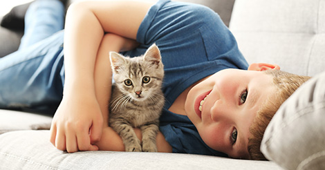 little-boy-holding-kitten-on-couch